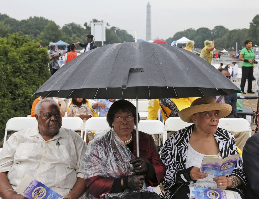 Stanley Samuels and Rita Samuels, from Atlanta, Ga., left, and Sammie Whiting-Ellis, from Washington, D.C., who attended the March on Washington 50 years ago where Martin Luther King, Jr., spoke, wait for the anniversary program to begin in front of the Lincoln Memorial in Washington, Wednesday, Aug. 28, 2013. (AP Photo/Charles Dharapak)