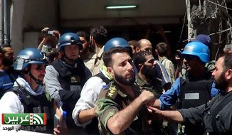 In this citizen journalism image provided by the United media office of Arbeen that has been authenticated based on its contents and other AP reporting, U.N. investigation team with blue helmets, walk with Syrian rebels in Damascus countryside of Zamalka, Syria, on Aug. 28, 2013. U.N. chemical weapons experts headed to a Damascus suburb on Wednesday for a new tour of areas struck by a purported poison gas attack, activists said, as Western powers laid the groundwork for a possible punitive strike and the U.N. chief pleaded for more time for diplomacy. (Associated Press/United media office of Arbeen)