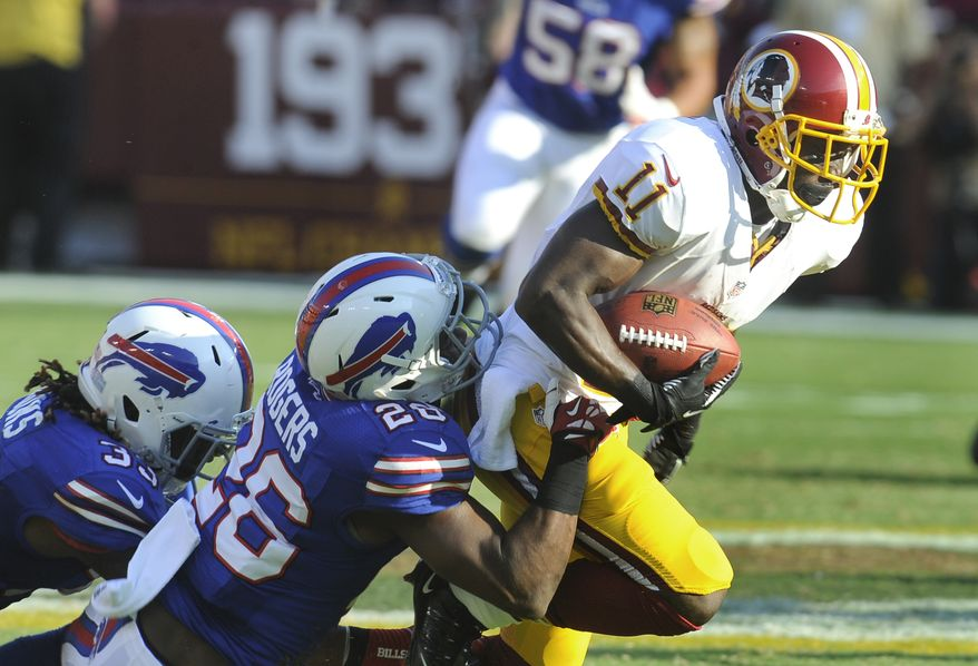 Redskins' receiver Aldrick Robinson (11) plows forward as he drags Bills' defenders Ron Brooks, left, and Justin Rogers (26) in their NFL preseason football game, Saturday, Aug. 24, 2013, in Landover, Md. Redskins defeated the Bills 30-7. (AP Photo/Richard Lipski)