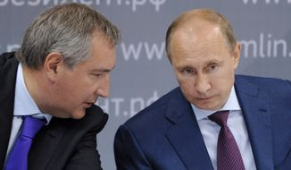 Russian President Vladimir Putin (right) and Deputy Prime Minister Dmitry Rogozin attend a meeting while visiting the Rostvertol helicopter manufacturing company in Rostov-on-Don, Russia, on Thursday, Aug. 22, 2013. (AP Photo/RIA-Novosti, Alexei Nikolsky, Presidential Press Service)