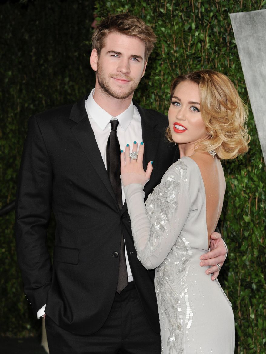 ** FILE ** This Feb. 26, 2012, file photo shows Miley Cyrus, right, and Liam Hemsworth at the Vanity Fair Oscar party in West Hollywood, Calif. (AP Photo/Evan Agostini, file)