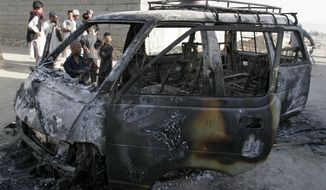 Afghans investigate the remains of a burned-out vehicle after a suicide attack in Afghanistan's Ghazni province on Thursday, Aug. 29, 2013. The Taliban launched their most complex attack this year — a failed effort to overrun a NATO base in the province that killed one U.S. soldier and wounded 10 Polish soldiers and dozens of Afghans. (AP Photo/Rahmatullah Nikzad)