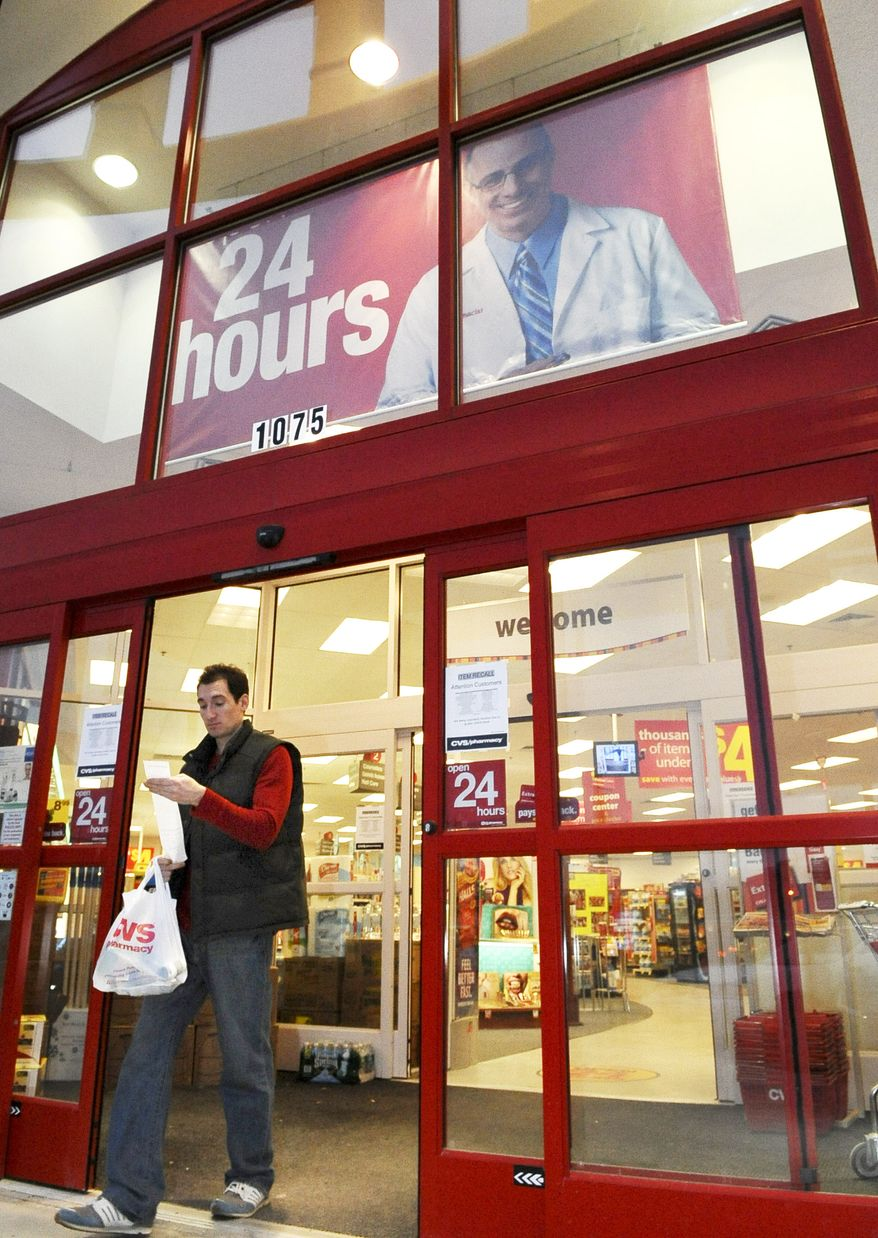 **FILE** Andrew Nathanson, of Peabody, Mass., looks at his receipt as he exits a CVS Caremark pharmacy in Saugus, Mass., on Feb. 18, 2009. (Associated Press)