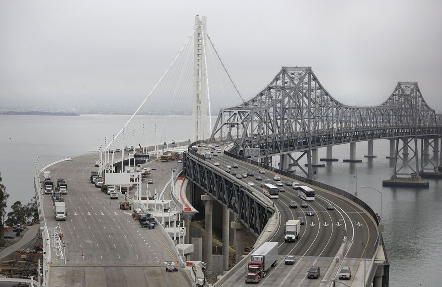 ** FILE ** Traffic drives along the eastern section of the San Francisco-Oakland Bay Bridge as work vehicles are parked along the new eastern section at left in San Francisco, Wednesday, Aug. 28, 2013. (AP Photo/Jeff Chiu)