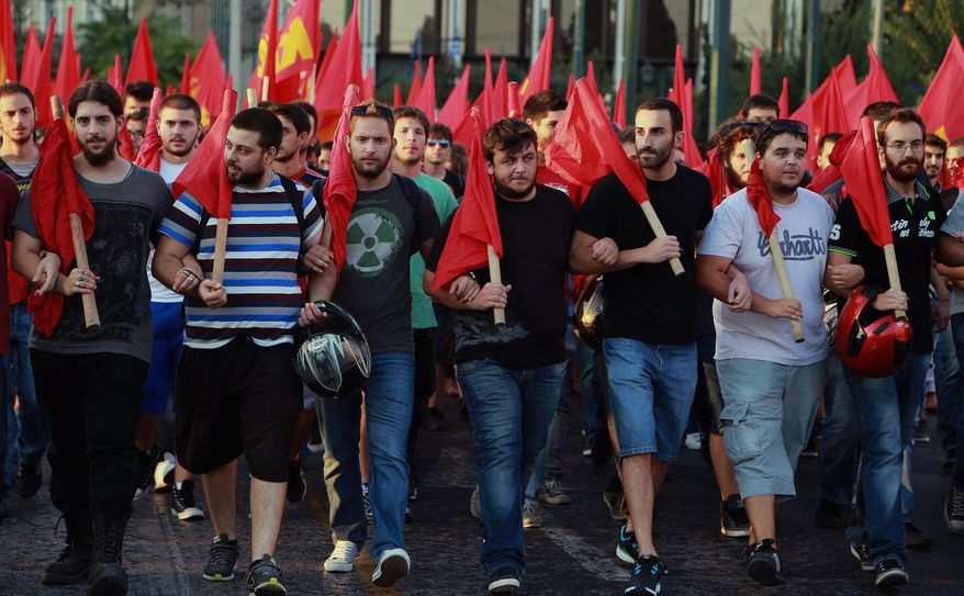 Members of the Greek Communist Party march with flags,  in front of the Parliament in Athens during an protest against any military action by the U.S. and its allies against Syria,  on Thursday Aug. 29, 2013. (AP Photo/Dimitri Messinis)