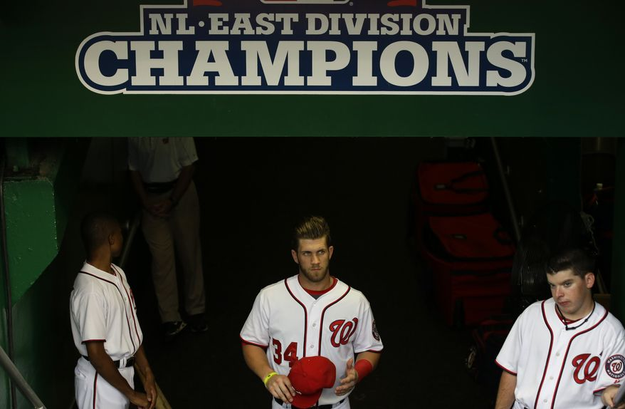 Washington Nationals Bryce Harper (34) stands near the steps to enter the dugout from the clubhouse before a baseball game against the Miami Marlins at Nationals Park Wednesday, Aug. 28, 2013, in Washington. (AP Photo/Alex Brandon)