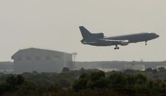A plane flies over Akrotiri British RAF airbase near Limassol, Cyprus, Thursday, Aug. 29, 2013. (AP Photo/Pavlos Vrionides)