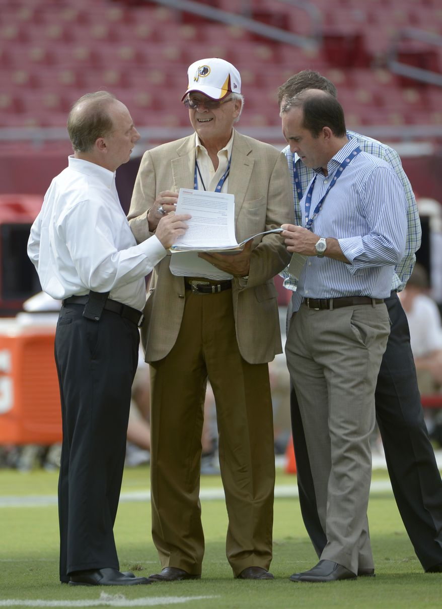 Washington Redskins team physician Dr. Tony Casolaro, left, and surgeon Dr. James Andrews look through paperwork while watching quarterback Robert Griffin III warms up before a preseason NFL football game against the Tampa Bay Buccaneers in Tampa, Fla., Thursday, Aug. 29, 2013.(AP Photo/Phelan M. Ebenhack)