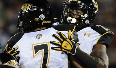 Towson quarterback Peter Athens (7) celebrates with Towson line backer Sterlin Phifer after Phifer scored a touchdown during the first half of an NCAA college football game at Rentschler Field in East Hartford, Conn., Thursday, Aug. 29, 2013. (AP Photo/Jessica Hill)