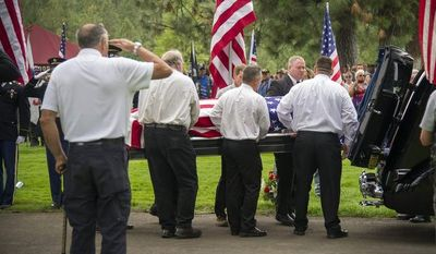 Pallbearers remove Delbert Belton's casket from a hearse during a graveside service, Thursday, Aug. 29, 2013, in Greenwood Memorial Terrace in Spokane, Wash. The World War II veteran Belton, who died, Aug. 21, 2013, after being beaten to death during a robbery, was buried with full military honors. (AP Photo/The Spokesman-Review, Colin Mulvany)