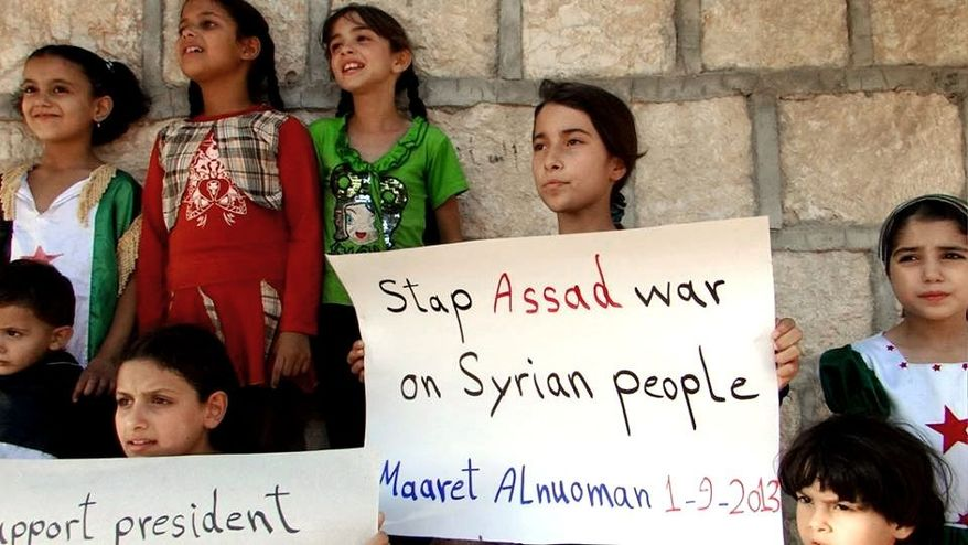In this Sunday, Sept. 1, 2013, citizen journalism image provided by Edlib News Network, ENN, which has been authenticated based on its contents and other AP reporting, Syrian children hold signs during a demonstration in Maaret al-Numan, Idlib province, northern Syria. (AP Photo/Edlib News Network ENN)