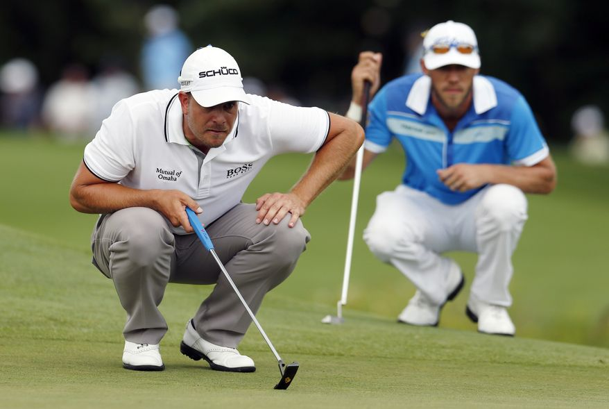 Henrik Stenson, left, of Sweden, lines up a putt on the second hole as Graham DeLaet looks on during the final round of the Deutsche Bank Championship golf tournament in Norton, Mass., Monday, Sept. 2, 2013. (AP Photo/Michael Dwyer)