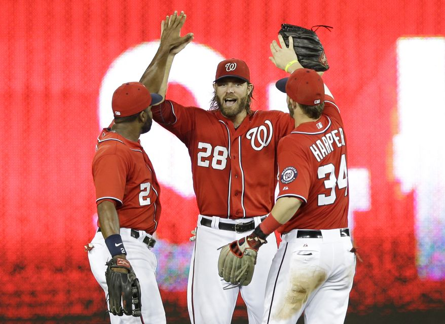 Jayson Werth, center, celebrates the Nationals' comeback victory with Bryce Harper, right, and Denard Span, left. (Associated Press photo)