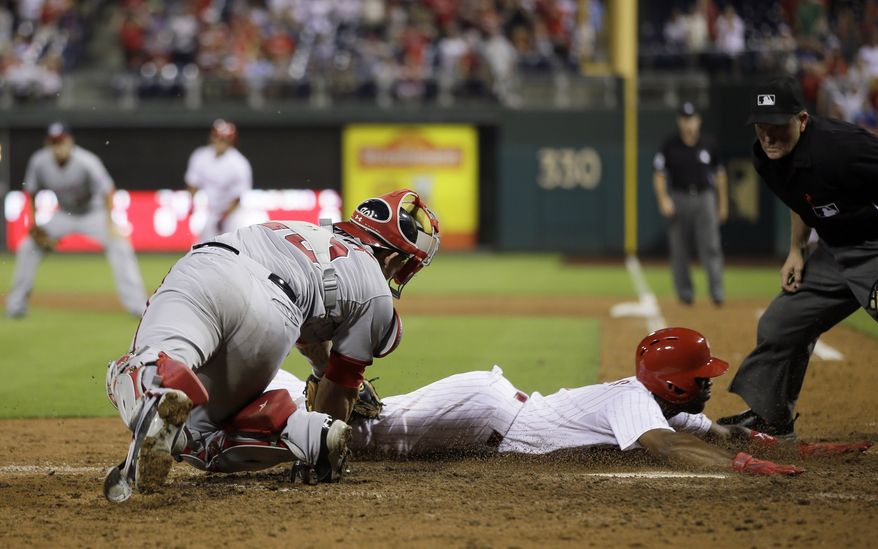 Washington Nationals catcher Wilson Ramos tries to sweep the tag on Philadelphia Phillies shortstop Jimmy Rollins as he scores the decisive run in the Nationals 3-2 loss. (Associated Press photo)