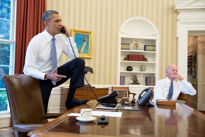 President Barack Obama talks on the phone in the Oval Office with Speaker of the House Boehner, Saturday, August 31, 2013. Vice President Joe Biden listens at right. (credit: White House photo/Pete Souza)