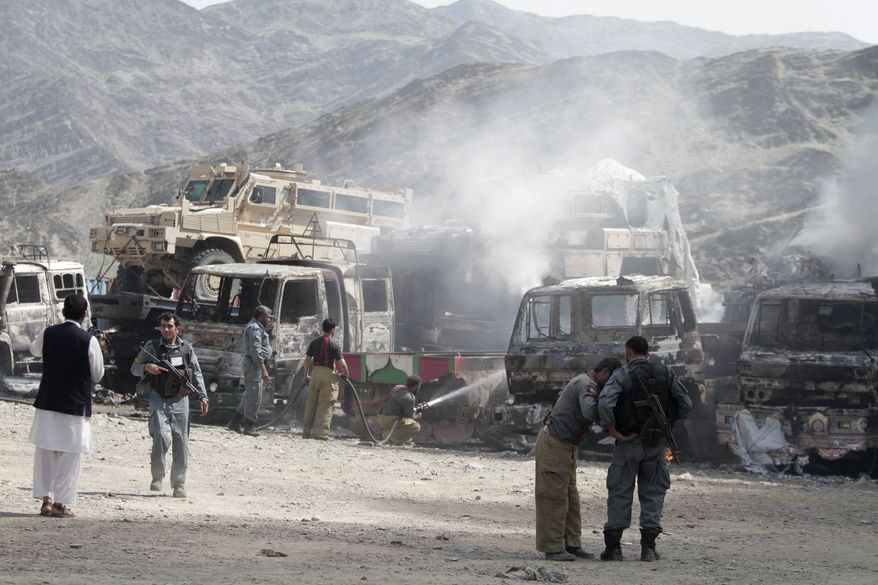 Afghan policeman stand guard near burning NATO supply trucks following an attack by militants on a U.S. base in the Torkham area near the Pakistan-Afghanistan border in Jalalabad province east of Kabul, Afghanistan, Monday, Sept. 2, 2013. (AP Photo/Rahmat Gul)