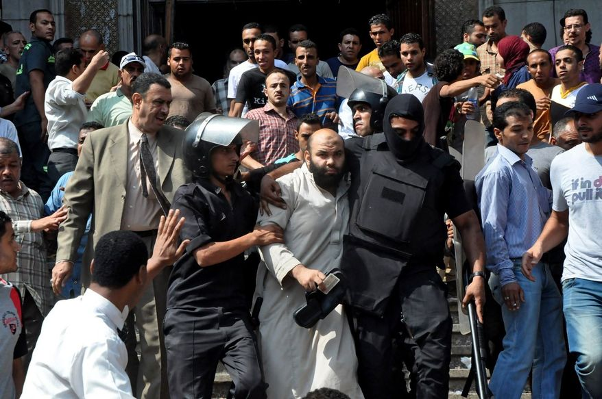 ** FILE ** Egyptians security forces escort an Islamist supporter of the Muslim Brotherhood out of the al-Fatah mosque, after hundreds of Islamist protesters barricaded themselves inside the mosque overnight, following a day of fierce street battles that left scores of people dead, near Ramses Square in downtown Cairo, Egypt, Saturday, Aug. 17, 2013. (AP Photo/Hussein Tallal)