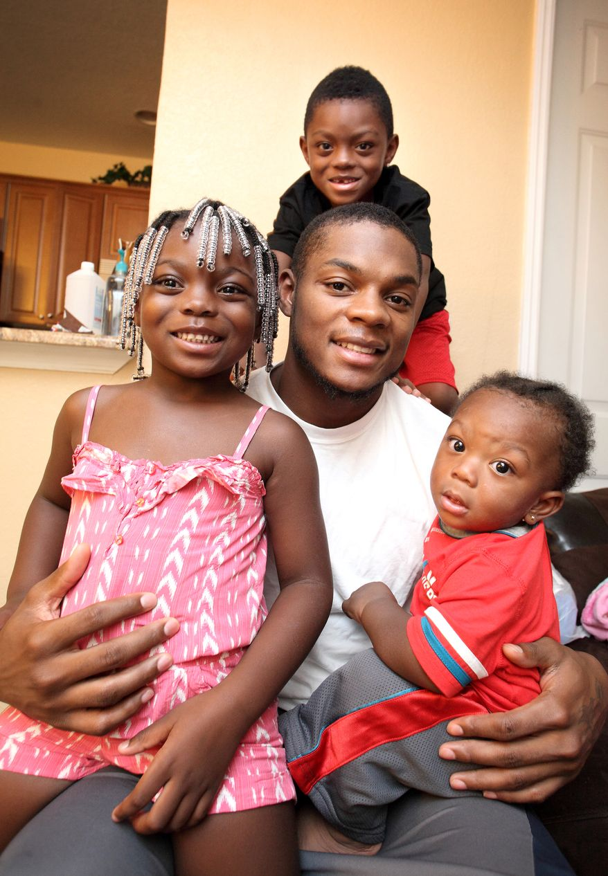 Redskins receiver Leonard Hankerson is surrounded by his children Leonard III, Lenaris and Kienarria.  Hankerson, whose father was murdered before he was born, is determined to be a strong presence in his children's life beyond his earning power as a pro football player. (Cristobal Herrera/For The Washington Times)