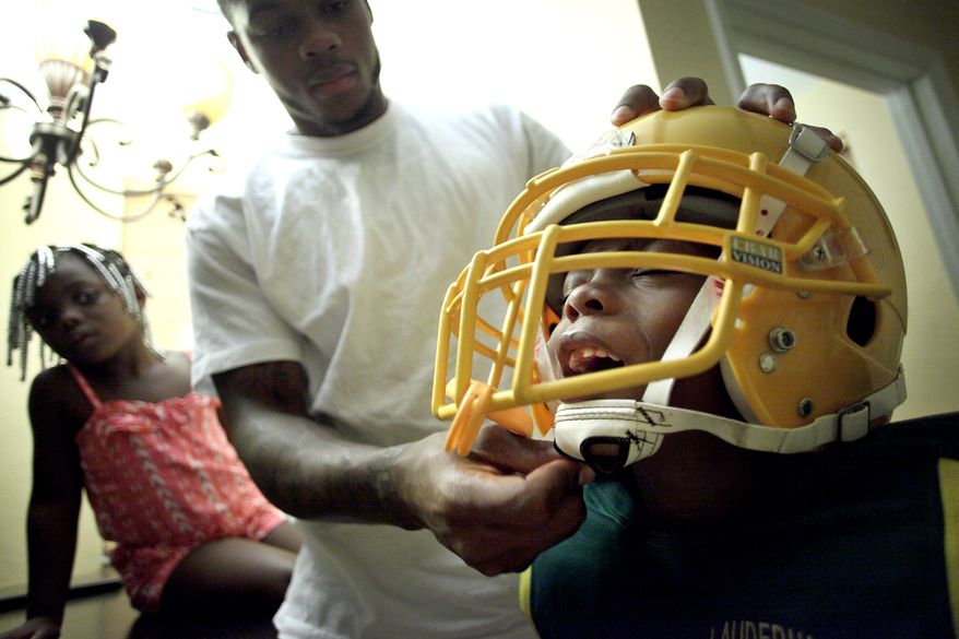 Washington Redskins wide receiver Leonard Hankerson, centers, helps his child Leonard, 7, right, to wear a football helmet at their home in Lauderhill, Florida on July 18, 2013. Next to Hankerson is his daughter Kienarria, 4. (Cristobal Herrera/For The Washington Times)