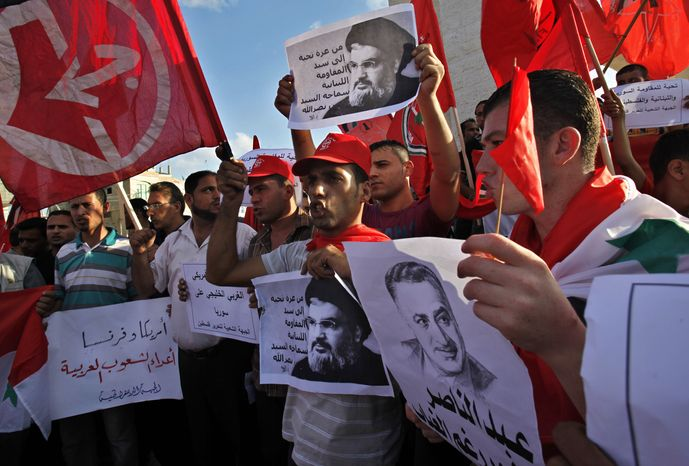 """Palestinian supporters of the Popular Front for the Liberation of Palestine wave their red flags in Rafah Refugee Camp, southern Gaza Strip, on Sept. 3, 2013, while holding Syrian flags and pictures of late Egyptian President Gamal Abdel-Nasser and Hezbollah leader Hassan Nasrallah during a protest against a possible military attack by the United States on Syria, . Arabic on placards reads, """"America and France are the enemies of the Arab nations, greetings from Gaza to the master of the Lebanese resistance, the leader Hassan Nasrallah and greetings to the Syrian, Lebanese and Palestinian resistance."""" (Associated Press)"""