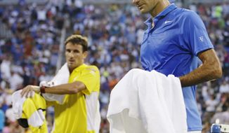 Roger Federer, of Switzerland, right, and Tommy Robredo, of Spain, walk off the court during a break in play during the fourth round of the 2013 U.S. Open tennis tournament, Monday, Sept. 2, 2013, in New York. (AP Photo/Darron Cummings)