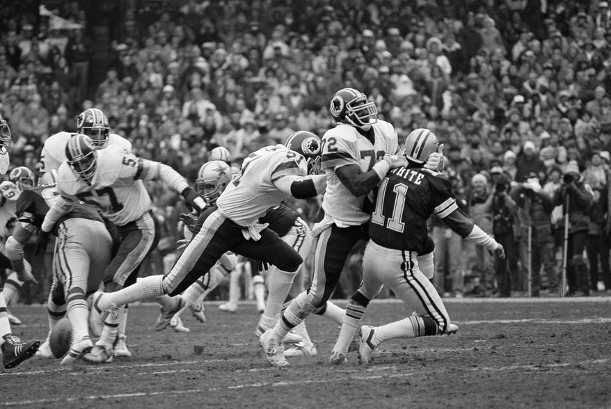 Dallas Cowboys quarterback Danny White (11), is hit hard by Dexter Manley (72) of the Washington Redskins just before the first half Saturday, Jan 22, 1983, at RFK Stadium in Washington. White was hurt on the play and left the game. (AP Photo)