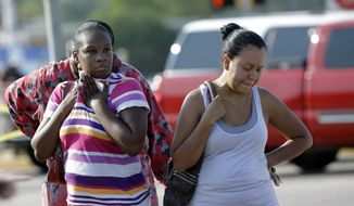 Eunice Pacheco (right) and LaKesia Brent wait for news about their children outside Spring High School on Wednesday, Sept. 4, 2013, in Spring, Texas, after a stabbing incident in the school cafeteria. (AP Photo/David J. Phillip)
