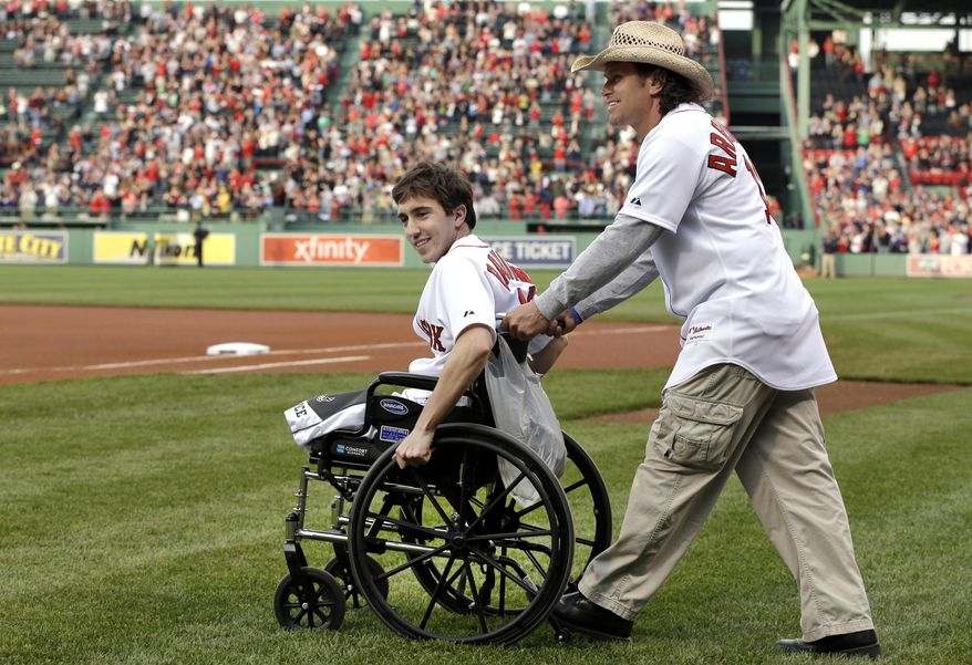 ** FILE ** Boston Marathon bombing survivor Jeff Bauman, left, is wheeled out by Carlos Arredondo, the man who helped save his life, to throw out the ceremonial first pitch at Fenway Park in a Tuesday, May 28, 2013, file photo, prior to a baseball game between the Boston Red Sox and the Philadelphia Phillies, in Boston. (AP Photo/Elise Amendola, File)