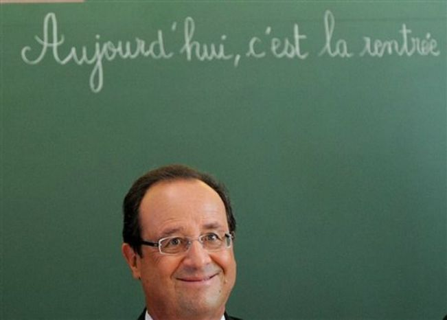 "French President Francois Hollande sits for a discussion as he visits the school Michelet for the start of the school year, in Denain, northern France, Tuesday, Sept. 3, 2013. The board reads : Today, it is the start of school year."" (AP Photo/ Denis Charlet, Pool)"