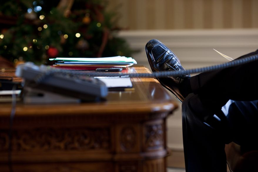 President Barack Obama rests his foot on the Resolute Desk during a call with British Prime Minister David Cameron in the Oval Office, Dec. 21, 2010. (Official White House Photo by Pete Souza)