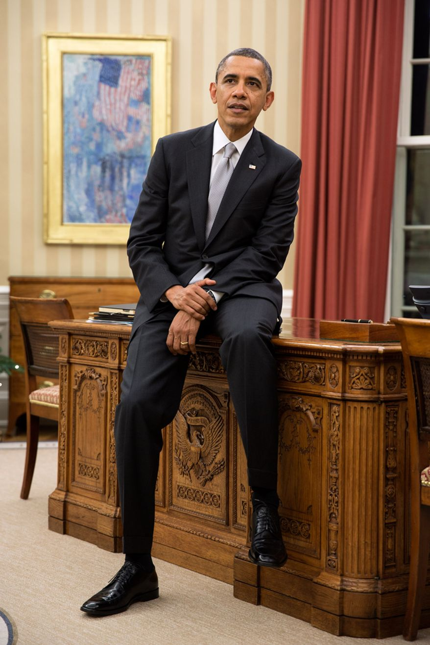 President Barack Obama sits on the edge of the Resolute Desk during a meeting in the Oval Office, Dec. 19, 2012. (Official White House Photo by Pete Souza)