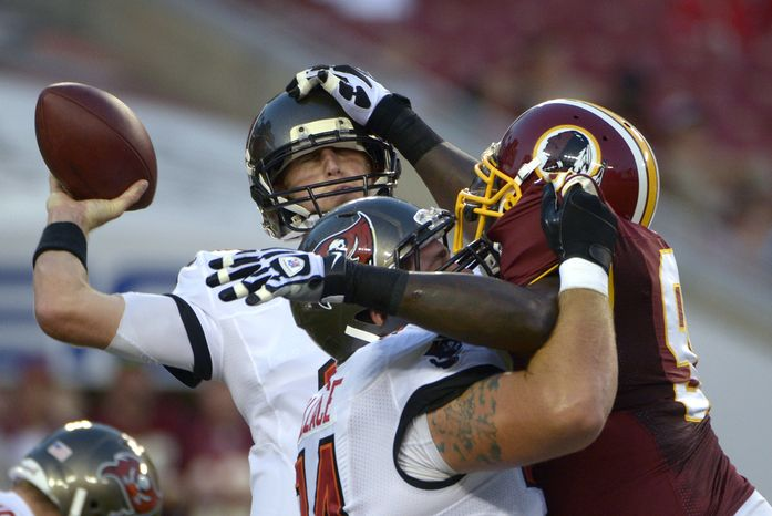 Washington Redskins defensive end Jarvis Jenkins (99) hits Tampa Bay Buccaneers quarterback Mike Glennon (8) on the helmet as he prepares to throw during the first quarter of an NFL preseason football game Thursday, Aug. 29, 2013, in Tampa, Fla. (AP Photo/Phelan M. Ebenhack)