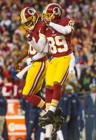 Wide receiver Santana Moss celebrates with Robert Griffin III after Griffin threw a touchdown in the wild-card playoff game against Seattle in January. Though the veteran caught only 41 passes in 2012, eight went for TDs. (andrew harnik/the washington times)