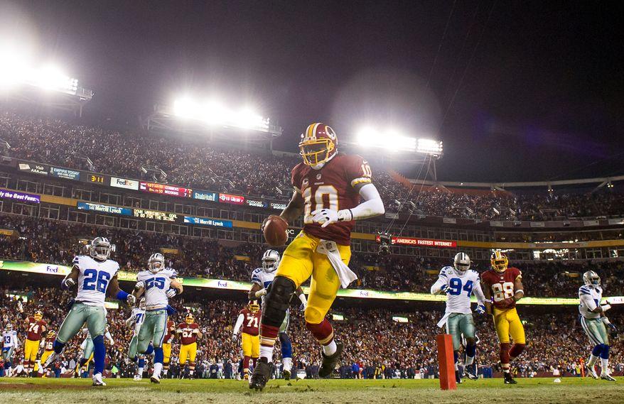 Washington Redskins quarterback Robert Griffin III (10) keeps it himself and scores on a 10 yard run in the third quarter as the Washington Redskins play the Dallas Cowboys at FedEx Field, Landover, Md., Sunday, December 30, 2012. (Andrew Harnik/The Washington Times)
