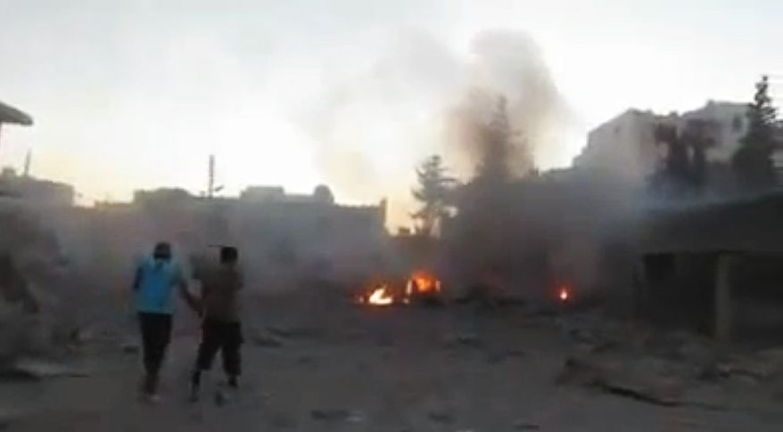 In this image taken from video obtained from the Shaam News Network, which has been authenticated based on its contents and other AP reporting, Syrian men walk near damages after a bomb hit Binnish town, Idlib province, Syria, on Sept. 5, 2013. (Associated Press/Shaam News Network via AP video)