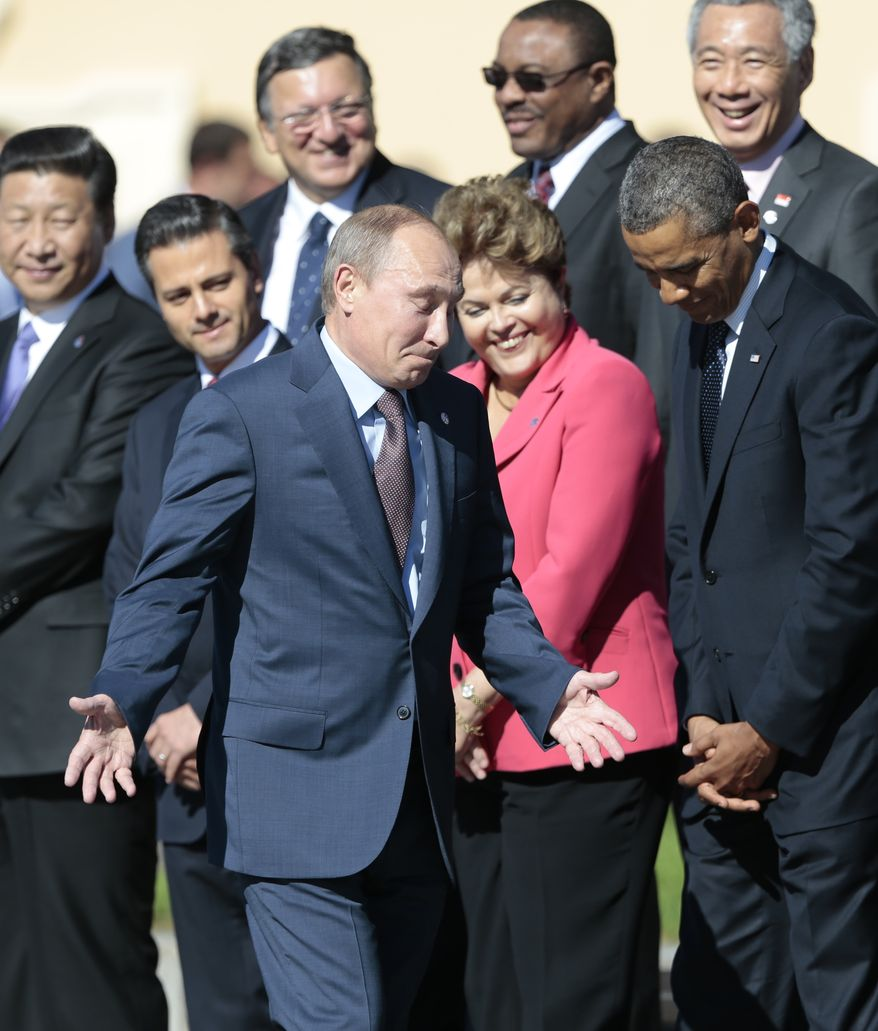 Russia's President Vladimir Putin, center foreground, gestures as he walks by U.S. President Barack Obama, front row right, as he takes his place at a group photo outside of the Konstantin Palace in St. Petersburg, Russia on Friday, Sept. 6, 2013. World leaders are discussing Syria's civil war at the summit but look no closer to agreeing on international military intervention to stop it. (AP Photo/Ivan Sekretarev)