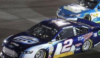 Brad Keselowski (2) runs in Turn 4 near David Stremme (30) during the NASCAR Sprint Cup Series auto race at Richmond International Raceway in Richmond, Va., Saturday, Sept. 7, 2013. (AP Photo/Zach Gibson)