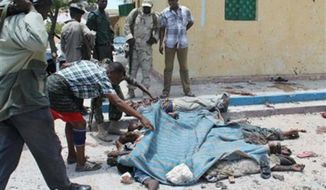 Somali soldiers look at the bodies of some of those who were killed in a suicide and car bomb blasts at a restaurant in Mogadishu, Somalia, Saturday, Sept, 7, 2013. (Farah Abdi Warsameh)