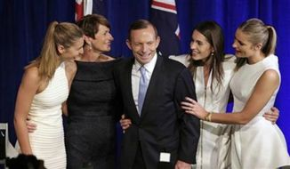Tony Abbott, third left, and his daughters Frances, left, Louise, second right, and Bridget, right, and his wife Margaret, second left, come to the stage to celebrate Tony's election victory in Sydney, Saturday, Sept. 7, 2013, following his win in Australia's national election. Australia's conservative opposition swept to power, ending six years of Labor Party rule and winning over a disenchanted public by promising to end a hated tax on carbon emissions, boost a flagging economy and bring about political stability after years of Labor infighting. (AP Photo/Rick Rycroft)
