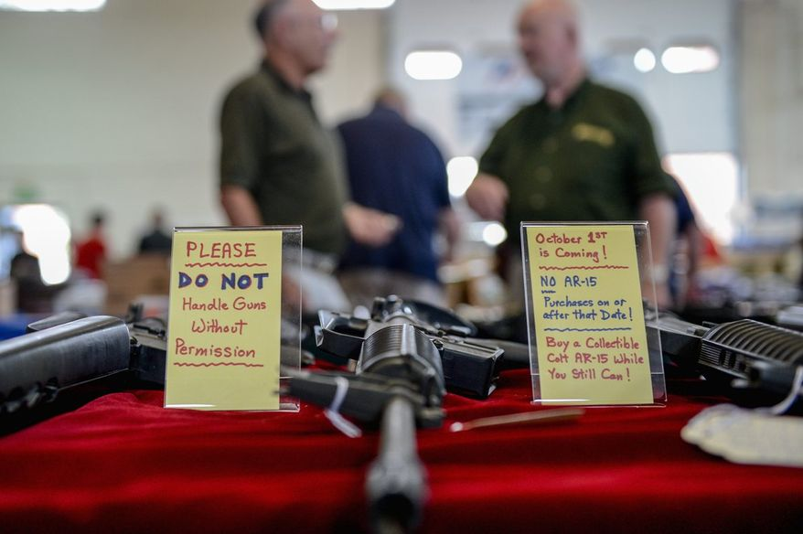 """** FILE ** In this Sept. 8, 2013, file photo, a sign warning of the coming assault weapons ban in Maryland is next to AR-15 semi-automatic rifles at the Annapolis Gun Show. """"You see people who've bought guns, you see older people. This is not about what everybody thinks it is. This is a plan to disarm America,"""" said Neil Kravitz of Appalachian Promotions. (Andrew Harnik/The Washington Times)"""