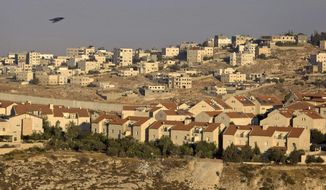The Jewish neighborhood of Pisgat Zeev is pictured in east Jerusalem in 2009, with the Shuafat refugee camp in the background and Israel's separation barrier running between them. (AP Photo/Sebastian Scheiner) FILE