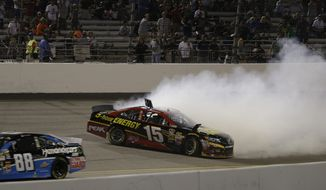 Clint Bowyer (15) spins out as Dale Earnhardt Jr. (88) passes by during the NASCAR Sprint Cup Series auto race at Richmond International Raceway in Richmond, Va., Saturday, Sept. 7, 2013. (AP Photo/Steve Helber)