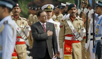 Outgoing Pakistani President Asif Ali Zardari (center) reviews honor guards during a farewell ceremony at President House in Islamabad on Sunday, Sept. 8, 2013. Mr. Zardari is stepping down at the end of his five-year term, becoming the first democratically elected president in the country's history to complete his full tenure in office. (AP Photo/Anjum Naveed)