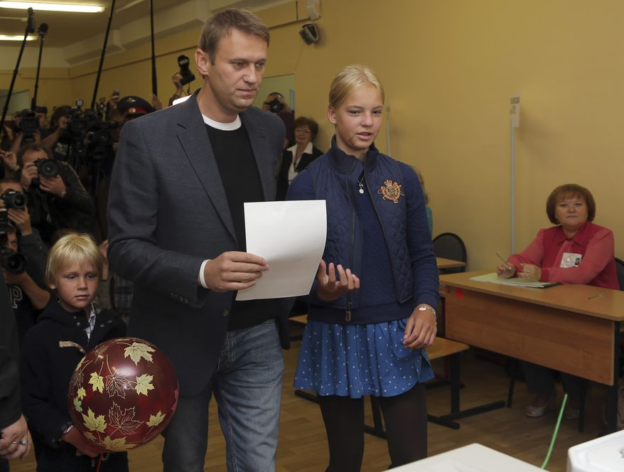 Russian opposition leader Alexei Navalny, with daughter Daria (right) and son Zakhar (left), prepares to vote in the mayoral election in Moscow on Sunday, Sept. 8, 2013. (AP Photo/Sergei Grits)