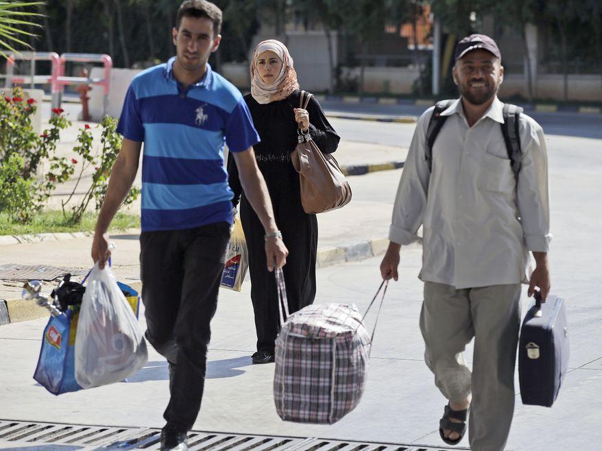 Syrian refugees arrive at Turkey's Cilvegozu border crossing on Sunday, Sept. 8, 2013. (AP Photo/Gregorio Borgia)