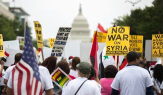 Anti-war activists march down Pennsylvania Avenue to voice opposition to proposed U.S. involvement in the Syrian civil war. (Andrew S. Geraci/The Washington Times)