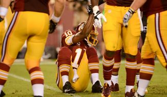 Washington Redskins quarterback Robert Griffin III (10) is helped up after a play in the third quarter as the Washington Redskins play the Philadelphia Eagles in Monday Night NFL football at FedExField, Landover, Md., Monday, September 9, 2013. (Andrew Harnik/The Washington Times)