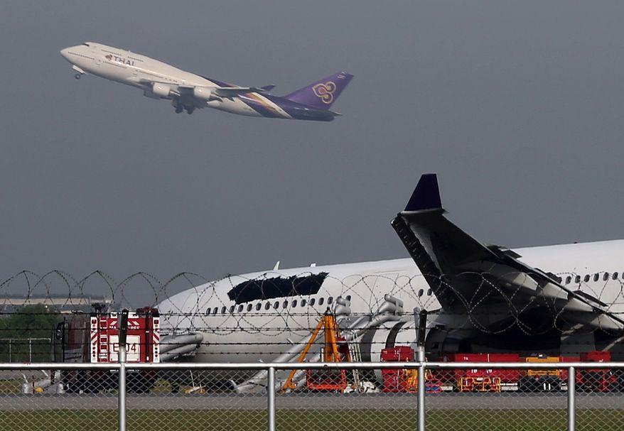 A Thai Airways passenger plane takes off over a damaged Thai Airways Airbus A330-300 at Suvarnabhumi International Airport in Bangkok, Thailand Monday, Sept. 9, 2013. (AP Photo/Apichart Weerawong)