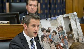 Rep. Adam Kinzinger (foreground), Illinois Republican, displays a photo of Syrian children while questioning Secretary of State John F. Kerry at a House Foreign Affairs Committee hearing on President Obama's request for congressional authorization for military intervention in Syria, a response to last month's alleged sarin gas attack in the Syrian civil war, on Capitol Hill in Washington on Wednesday, Sept. 4, 2013. Rep. Edward R. Royce, California Republican, who is the panel's chairman, listens at top. (AP Photo/J. Scott Applewhite)