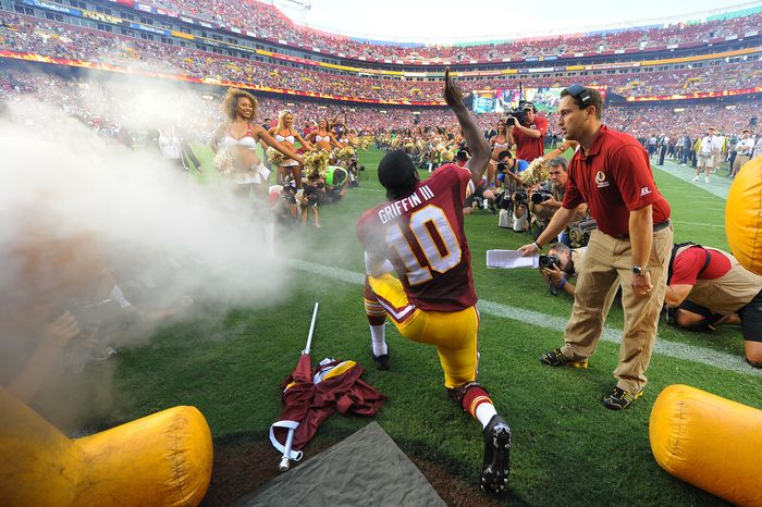 Washington Redskins quarterback Robert Griffin III (10) kneels on the field and points to the heavens as he's introduced for the first time in the 2013 season before the Washington Redskins play the Philadelphia Eagles in Monday Night NFL football at FedExField, Landover, Md., Monday, September 9, 2013. (Preston Keres / For The Washington Times)